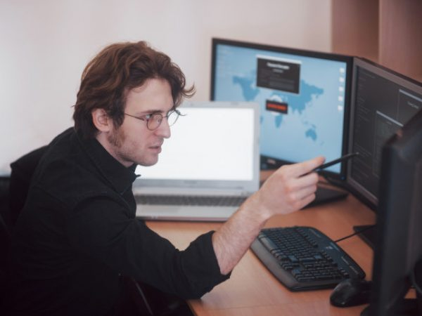 male-programmer-working-desktop-computer-with-many-monitors-office-software-develop-company-website-design-programming-coding-technologies_146671-9448